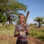 A young man in his father's sweet potato garden in the Soroti district of Uganda presents his working tools.