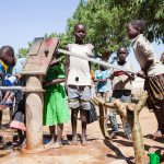 During the lunch break, schoolchildren pump drinking water from the school's own well in the Moroto district, one of the driest areas of Uganda.