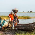 Lake Victoria is the third largest lake in the world and belongs to three African countries. A Ugandan fisherman carries her daily catch from the boat.