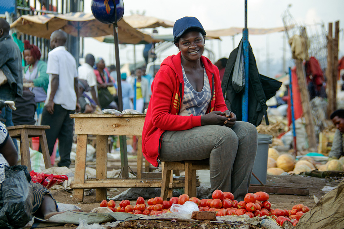 Barbara, a market seller, offers tomatoes and onions at her stand in Kalerwe. The tropical climate supports a rich harvest of vegetables.